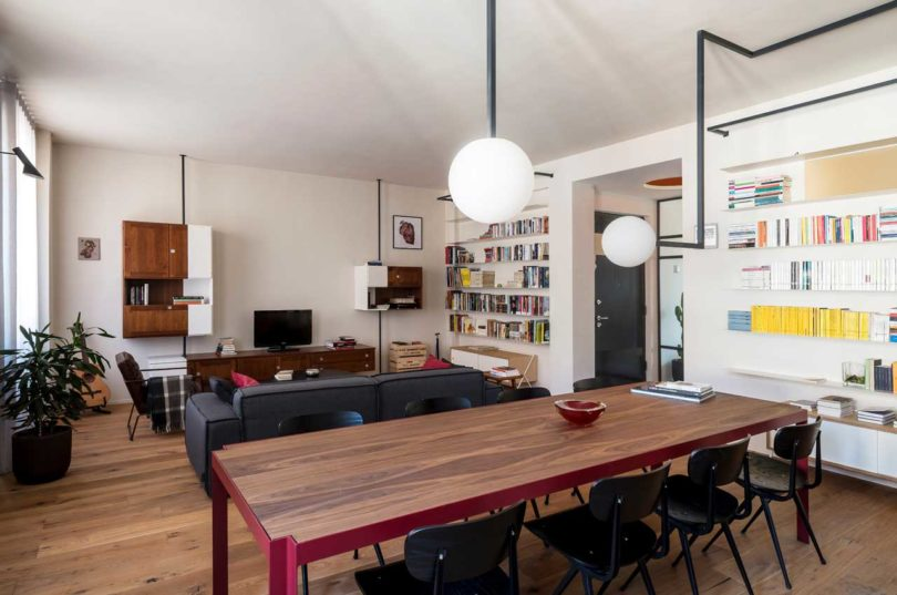 The living room is decorated with mid century modern furniture and some wall storage units, closed and opened ones