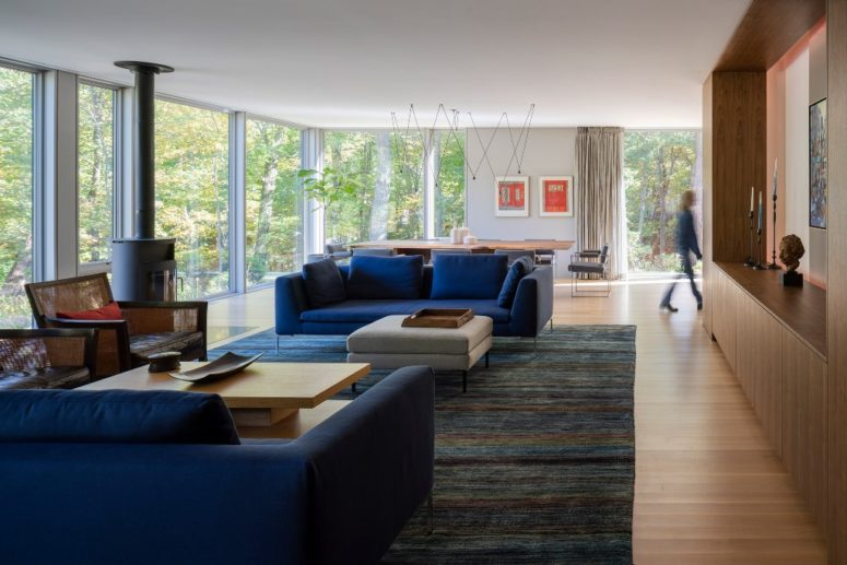 The living room is done with a heart, bold blue sofas and a glazed wall to unite with nature