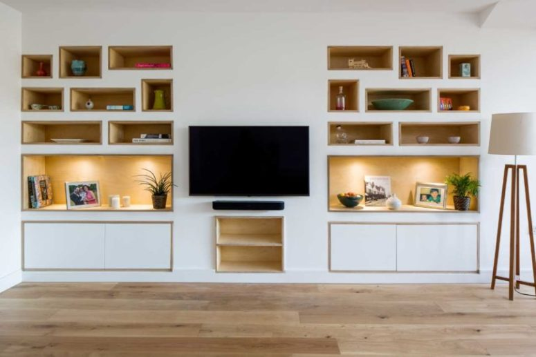 The living room is done with built-in shelves and a wall-mounted TV