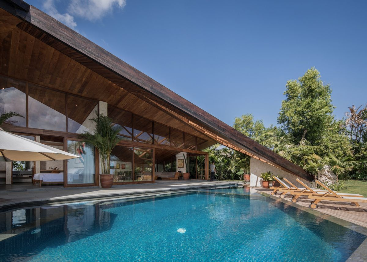 There's a small pool of a geometric shape, with a row of loungers and a gorgeous sea view