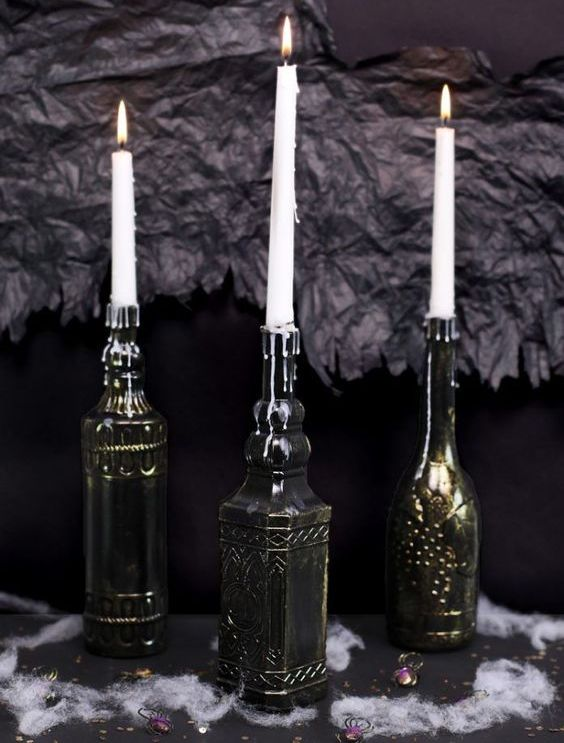 vintage bottles painted black and bronze to make the look like refined metal candleholders are chic and elegant