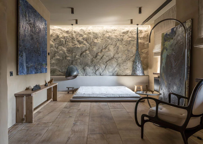 Another bedroom is full of art, there's a unique textural wall and creative pendant lamps