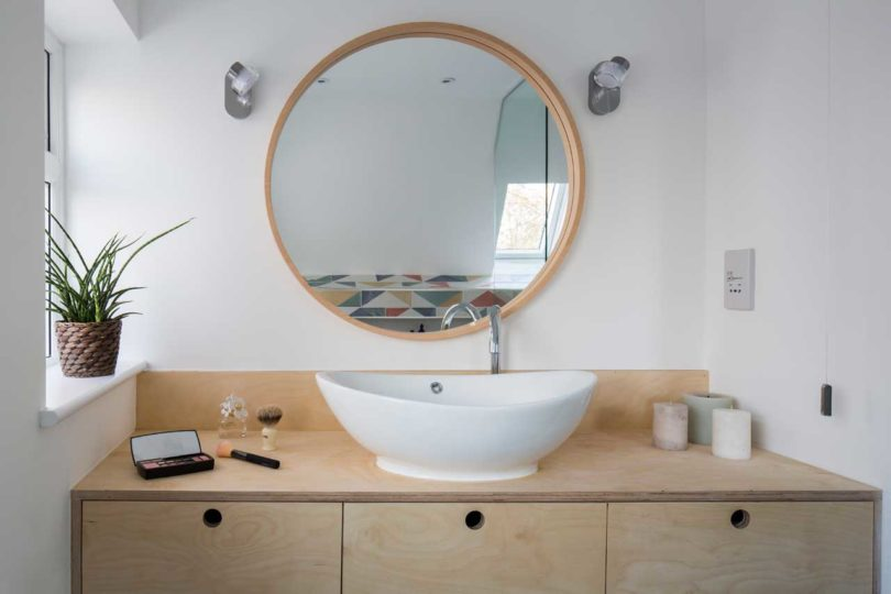 The bathroom is done with a plywood vanity, an oval sink and a round mirror