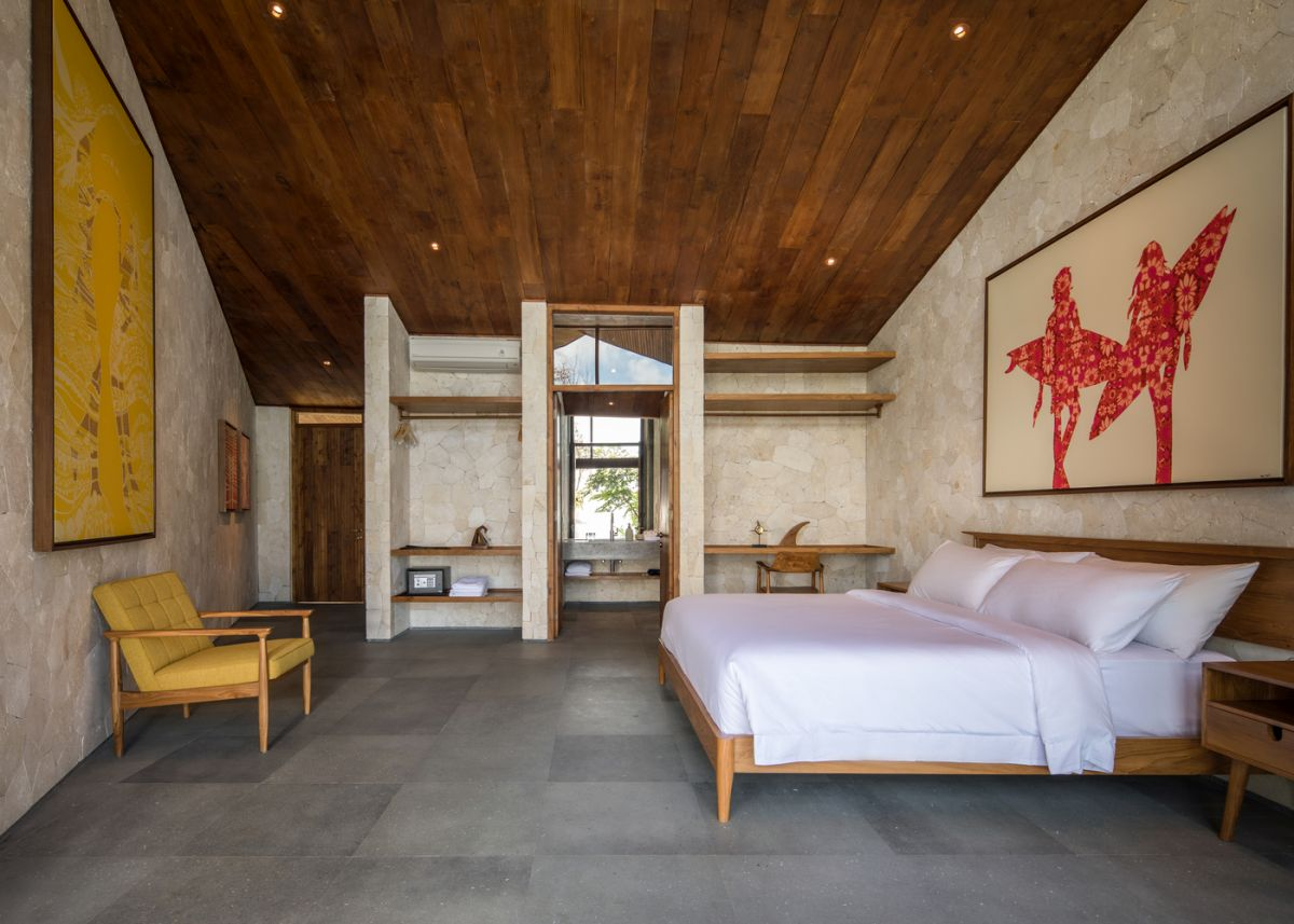 The bedroom is done in neutrals, a rich colored wood ceiling, modenr furniure and open storage space