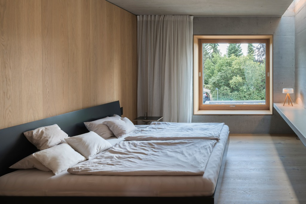 The bedroom is done with a black bed, some nightstands and a floating table