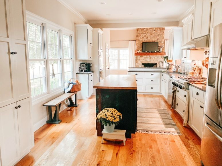 The kitchen is a light-filled space, with a brick backsplash, white cabinets and a black kitchen island