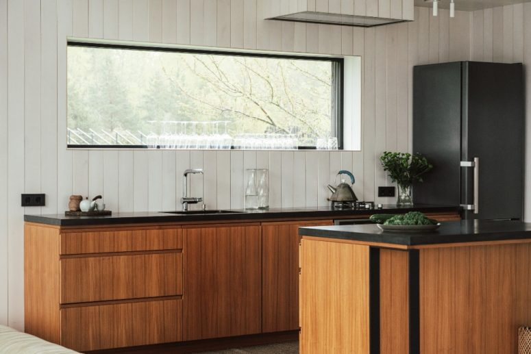 The kitchen is done with white walls, sleek plywood cabinets and black countertops plus a window to enjoy natural light and views