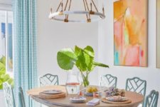 06 a white dining space infused with color using blue curtains and chairs and bright artworks on the wall