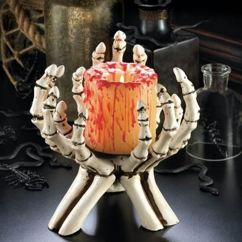 skeleton hands holding a bloody candle will be a nice decoration for a traditional Halloween party