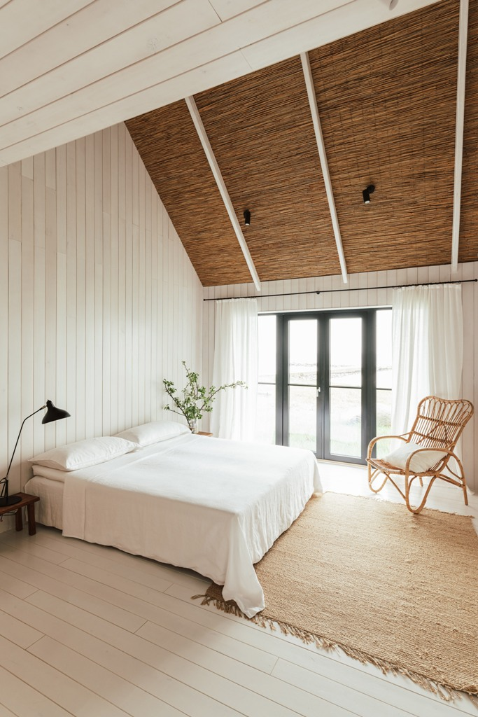 The bedroom is done with white plywood walls, an attic ceiling, a jute rug and a rattan chair plus some greenery and a glazed wall