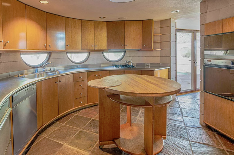 The kitchen is done with wooden cabinets of various shades coming in an arch and a round kitchen island in the center