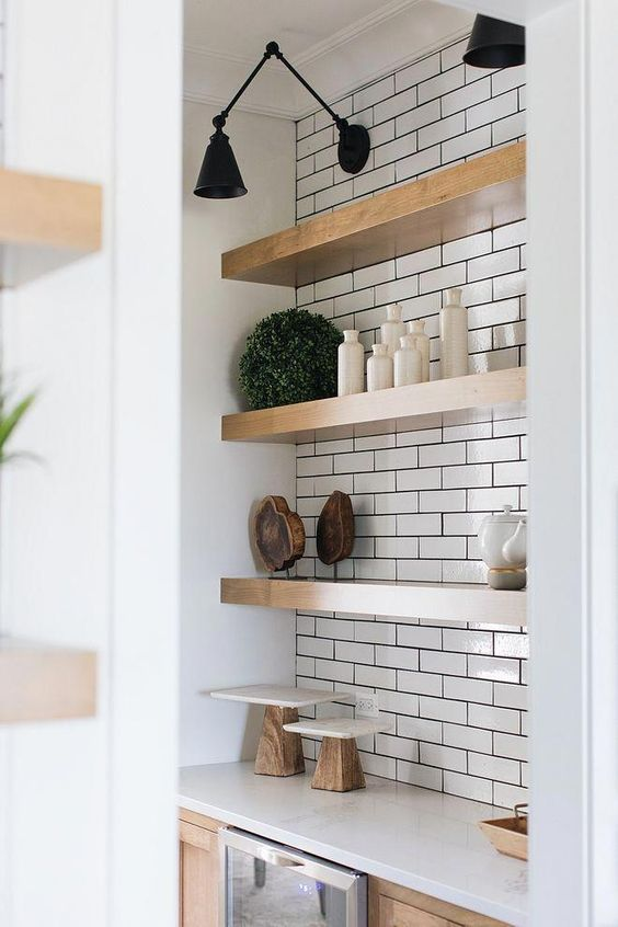 thick wooden shelves in a white tile niche look warming up and give a slight farmhouse feel to the space