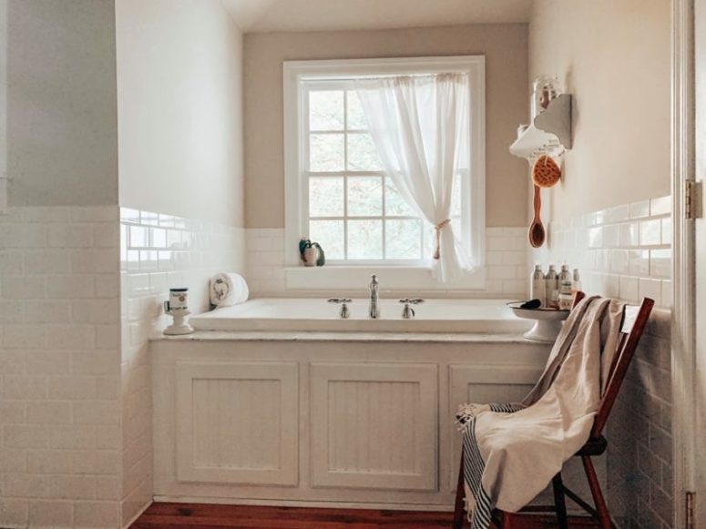 The bathroom is done in white, with a vintage tub and beadboards plus white subway tiles to make it cozy and chic
