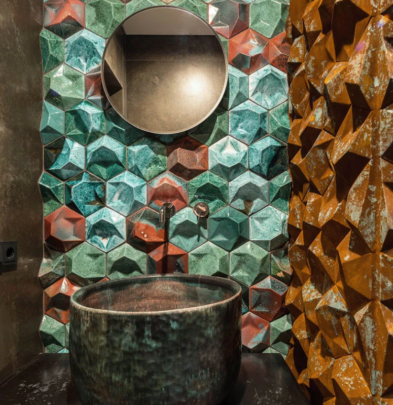 The bathroom is done with 3D porcelain tiles in rust, mustard and turquoise and a hammered metal sink
