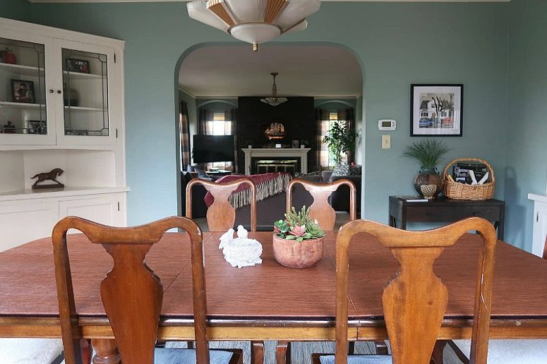 The dining room has blue walls, a vintage wooden furniture set, a corner buffet