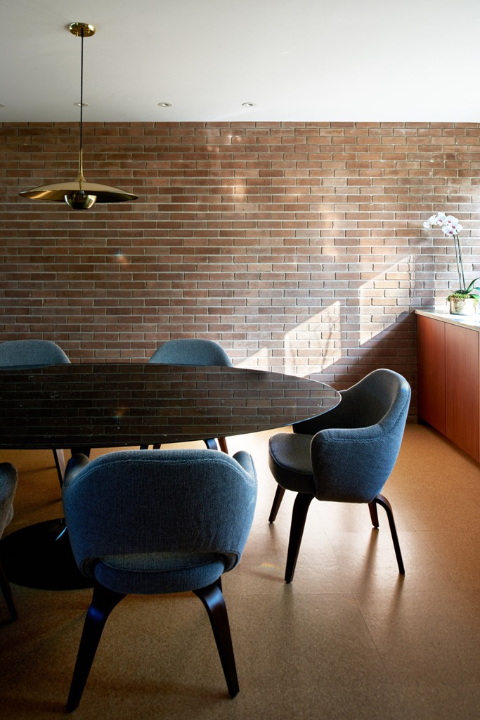 The dining space features a dark mirror table, blue chairs and a faux brick wall for a catchy look