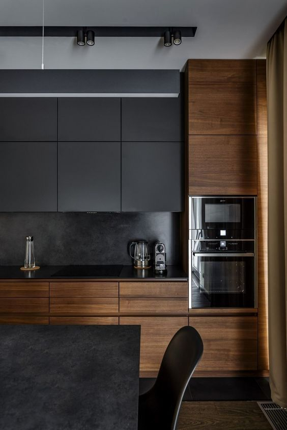 a dark black kitchen with sleek wooden cabinets that make it cozier and more welcoming