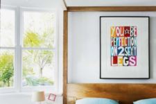 08 a white bedroom with natural wooden furniture is made brighter with blue bedding and a colorful artwork on the wall