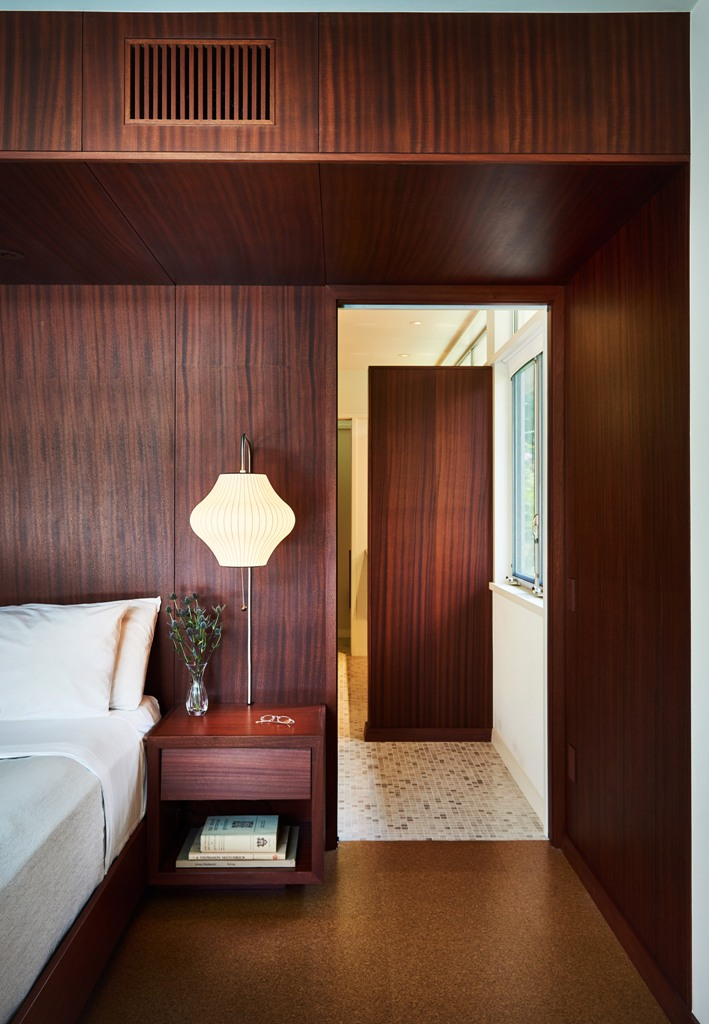 The bedroom is fully clad with mahogany, there are elegant lamps and a comfortable bed