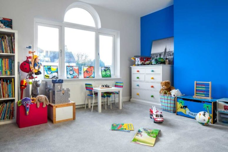 The kids' room is bright and fun, with a statement blue wall, with colorful posters and lots of toys