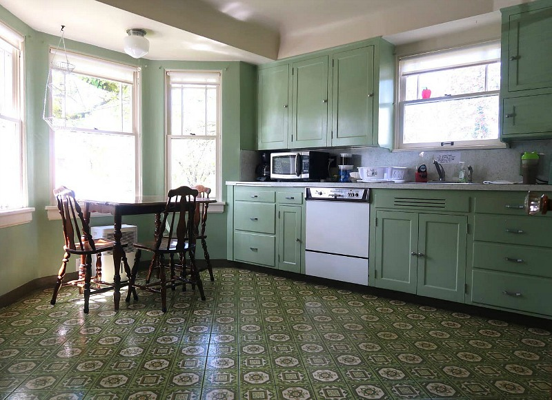 The kitchen is done in green, with vintage cabinets that originate from 1930s