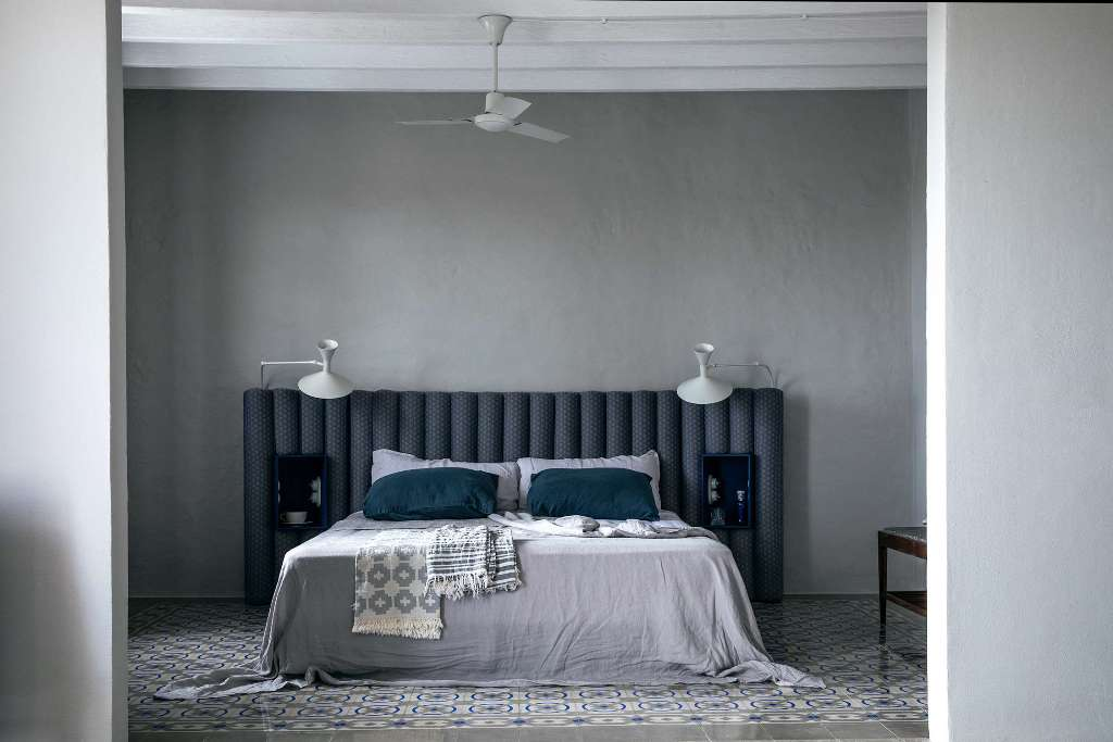 This bedroom is done in grey and teal, with matching tiles on the floor and an upholstered headboard