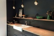 09 a minimalist black kitchen spruced up with a white sink and a wooden shelf plus countertops for a fresh look