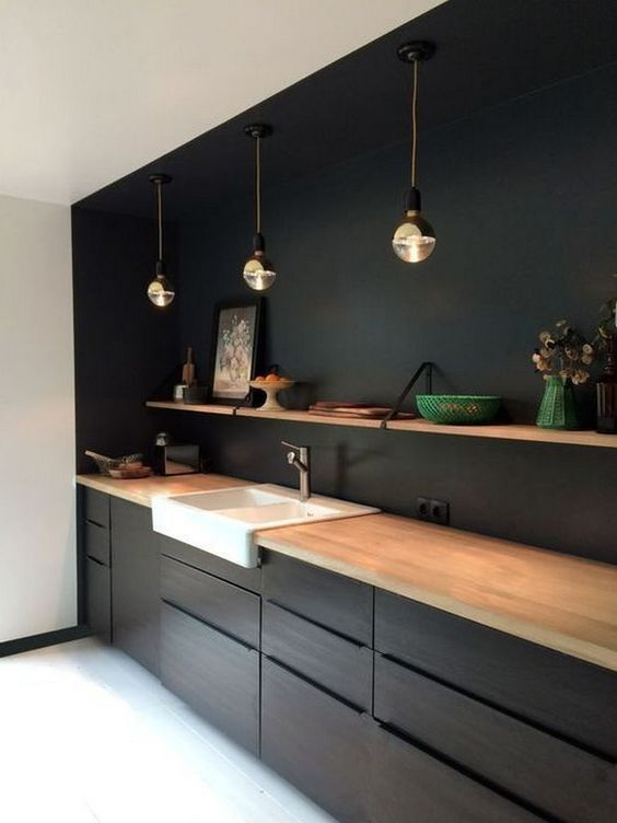 a minimalist black kitchen spruced up with a white sink and a wooden shelf plus countertops for a fresh look