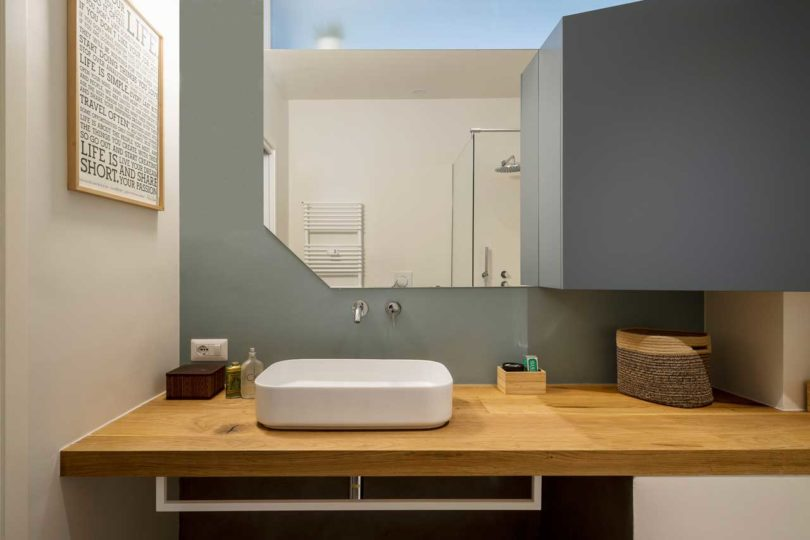 The bathroom continues the decor of the apartment with geometry and colors and some floating furniture
