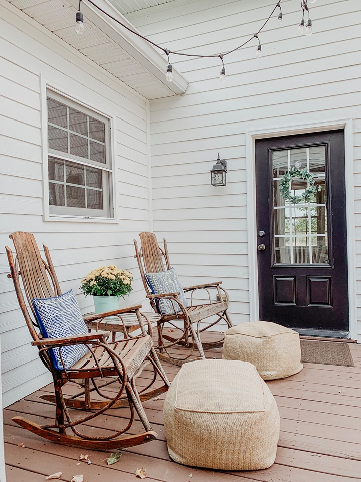 There's another porch done with burlap ottomans and wicker and wooden rockers