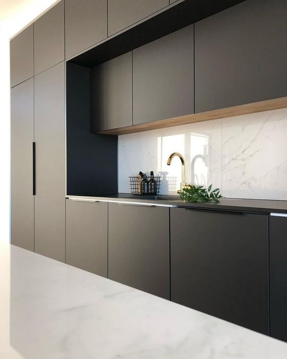 a minimalist black and white kitchen with a marble backsplash and a white floor looks bold and contrasting