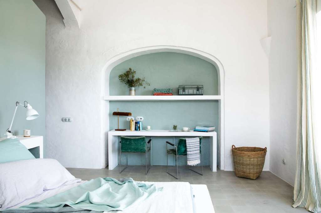 The bedroom is decorated in mint green and white, with a home office zone and a large bed