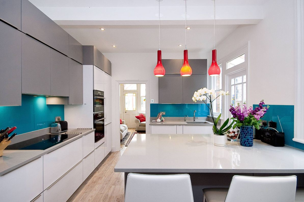 a minimalist open layout refreshed with bright blue ktchen backsplashes and bold red pendant lamps over the table