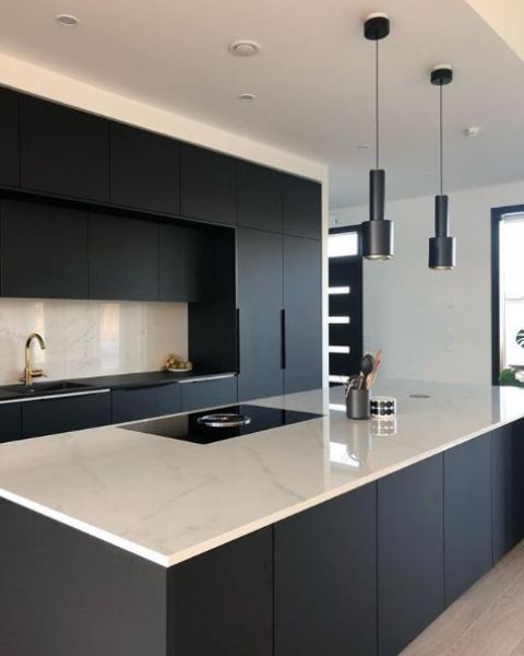 a stylish minimalist black and white kitchen with a white marble kitchen island countertop and a backsplash - just a bit of refreshing touches