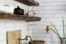 11 dark reclaimed wooden shelves look very bold and standing out in front of a white tile wall