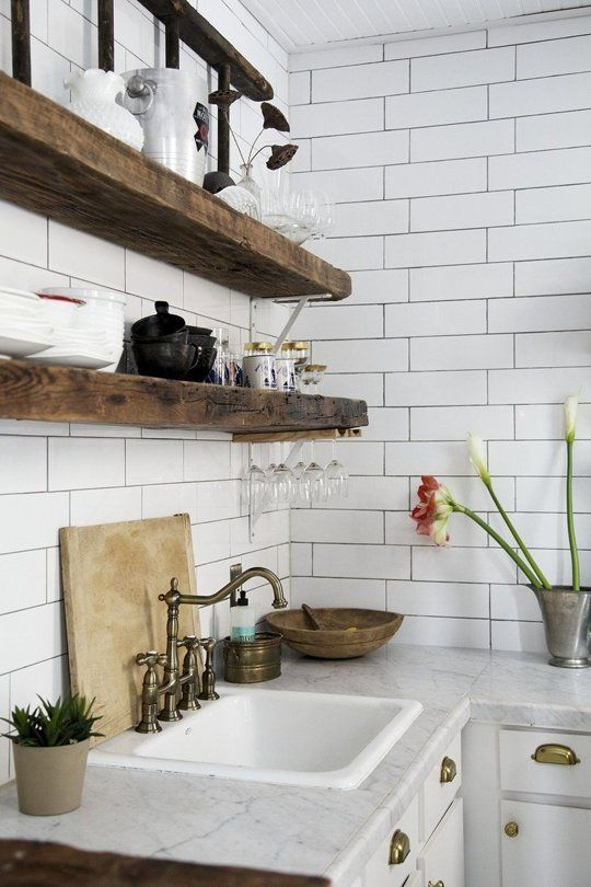 dark reclaimed wooden shelves look very bold and standing out in front of a white tile wall