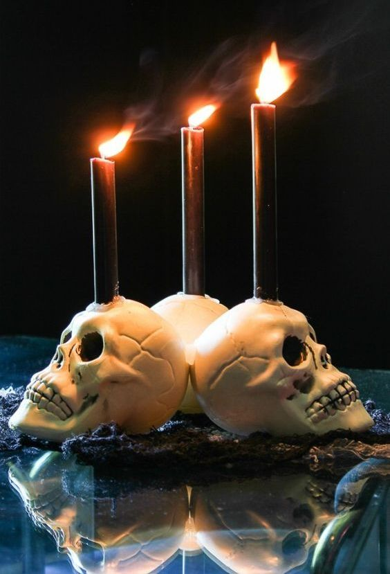 white skull candleholders with blakc candles are perfect for decorating your space for Halloween, simple and traditional