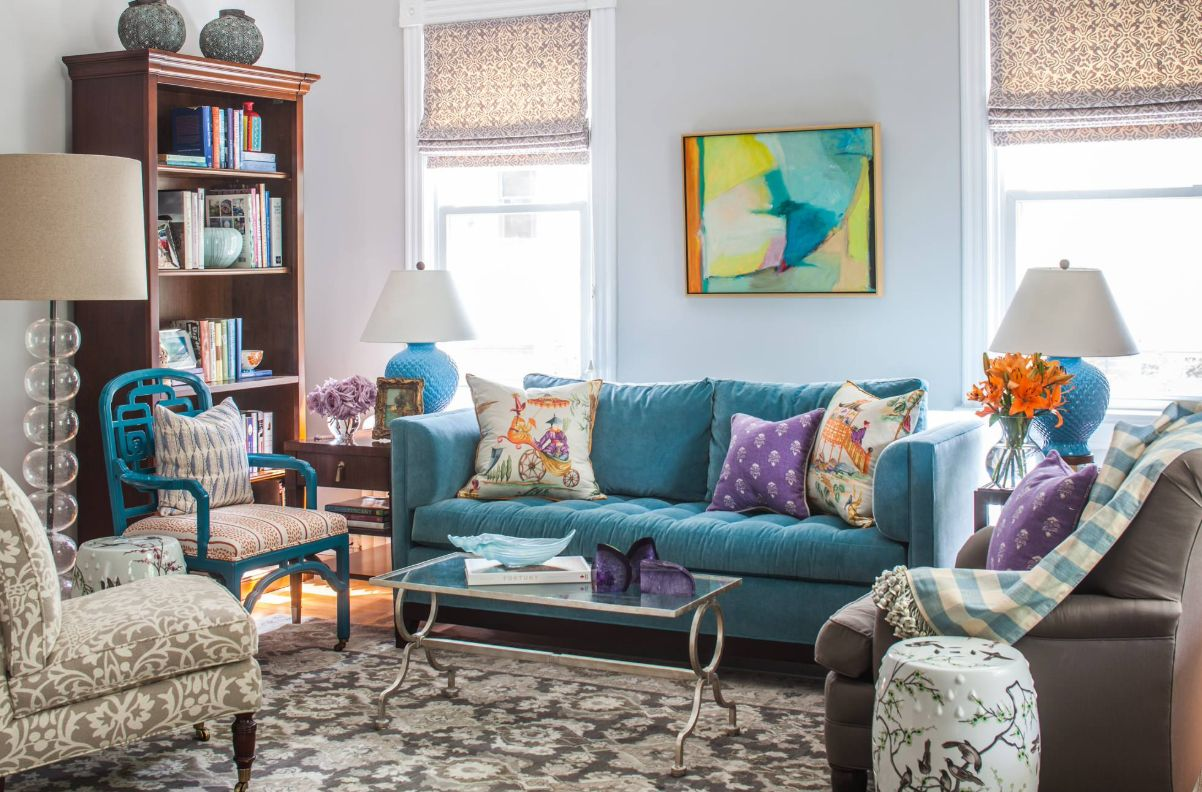 a super bright living room done with colorful furniture, artworks, blooms and accessories for a whimsy feel