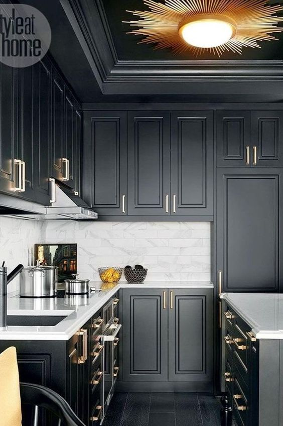 a black farmhouse kitchen refreshed wiith a white marble tile backsplash and metallic handles plus a sunburst lamp