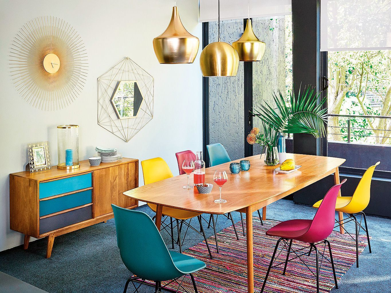 a bright mid century modenr dining space done with various shades of red, ble and metallics for a shiny touch
