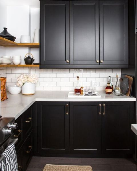 a black farmhouse kitchen refreshed with a white wall and a white subway tile backsplash for a contrasting look