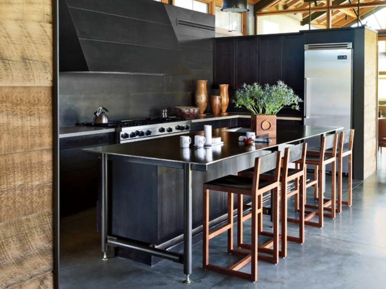 a black kitchen spruced up with copper stools looks much more welcoming and soft than without them