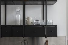 19 a black industrial shelving unit instead of upper cabinets is a stylish idea for a masculine and moody kitchen