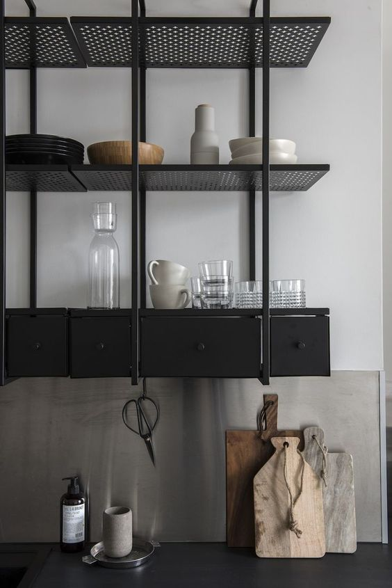 a black industrial shelving unit instead of upper cabinets is a stylish idea for a masculine and moody kitchen