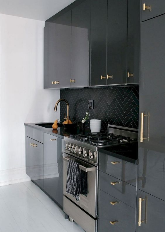 a modenr black kitchen refreshed with white surfaces and with gold handles all over that add a touch of glam