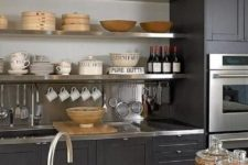 20 a black kitchen refreshed with a neutral backsplash, a wooden countertop and metal shelves, surfaces and faucets