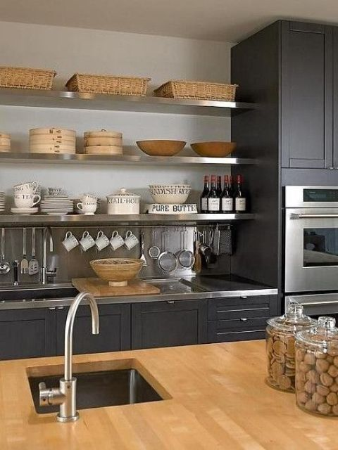 a black kitchen refreshed with a neutral backsplash, a wooden countertop and metal shelves, surfaces and faucets