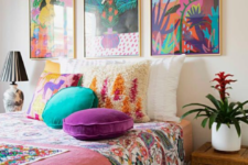 20 a colorful bedroom done in turquoise and purple, with colorful artworks over the bed, printed bedding and pillows