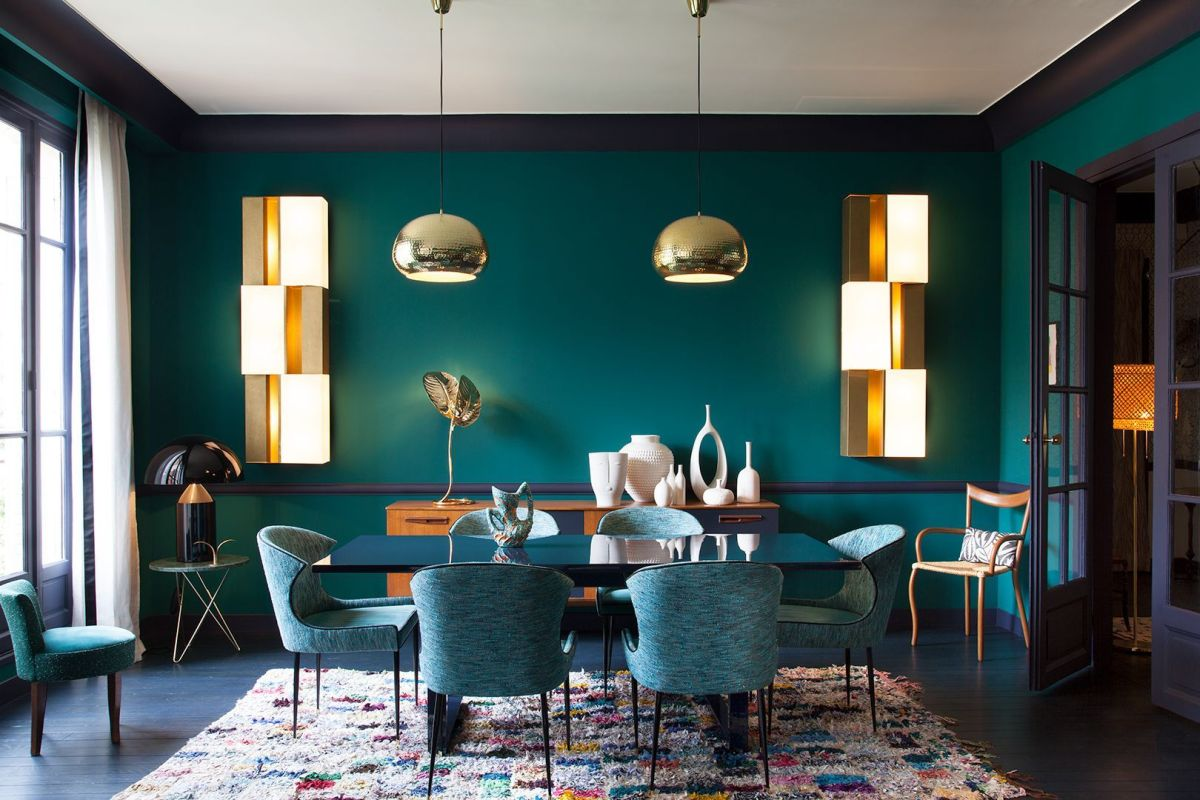 a bold monochromatic dining room done in blue and green, with metallic touches and with a colorful rug