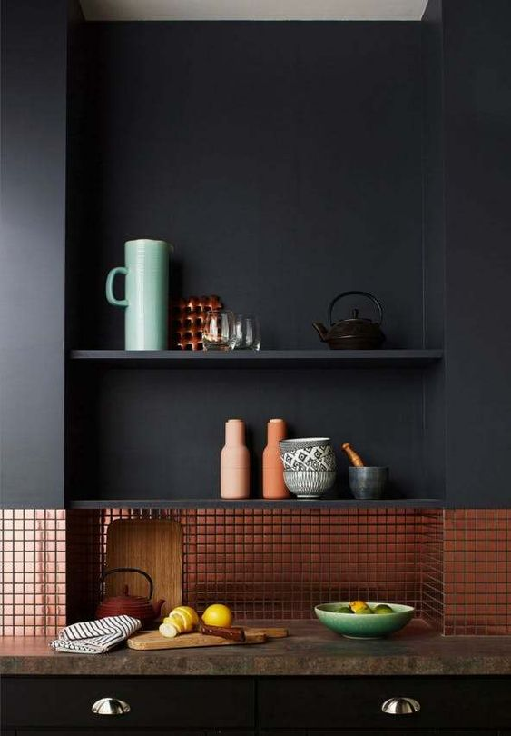 a stylish matte black kitchen made shiny with a cool copper tile backsplash that also adds warmth